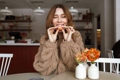 Изображение привлекательной кавказской женщины сидя на таблице, и еда Стоковая Фотография RF