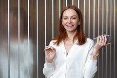 Изображение привлекательной коричневой с волосами молодой женщины в белых одеждах, работах в компании, держит сотовый телефон, от стоковые фотографии rf