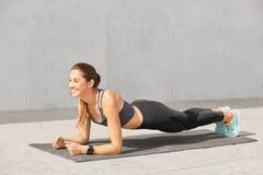 Изображение привлекательной молодой женщины с здоровым телом, представлениями на циновку в планке представляет, нажимает поднимае стоковые изображения
