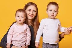 Изображение привлекательной усмехаясь женщины с близнецами маленьких девочек, carming daughrer носит случайно взгляд на камере, п стоковое фото