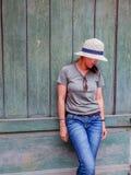 Изображение привлекательных азиатских женщин нося шляпу с зеленой винтажной деревянной предпосылкой стены стоковое изображение