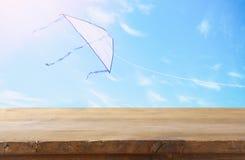 Изображение пустой деревенской таблицы перед красочным летанием змея в голубом небе через облака Для представления дисплея продук Стоковое фото RF