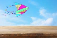 Изображение пустой деревенской таблицы перед красочным летанием змея в голубом небе через облака Для представления дисплея продук Стоковая Фотография