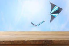 Изображение пустой деревенской таблицы перед красочным летанием змея в голубом небе через облака Для представления дисплея продук Стоковое Фото