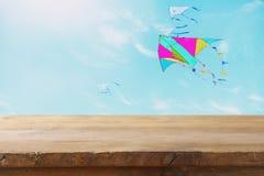 Изображение пустой деревенской таблицы перед красочным летанием змея в голубом небе через облака Для представления дисплея продук Стоковое Изображение RF