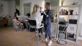 Изображение рабочего дня внутри красоты сидит на молодой женщине клиента стула красивой Художник состава делая состав в a сток-видео