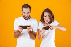 Изображение радостного человека и женщины играя совместно видеоигры на смартфонах, изолированное над желтой предпосылкой стоковая фотография