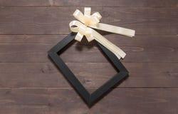 Изображение рамки и белая лента на деревянной предпосылке с Стоковое Фото
