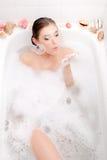 Изображение расслабляющей красивой молодой женщины лежа в ванне курорта с пузырями мыла пены и раковины дуя Стоковое фото RF