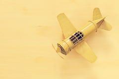 изображение ретро самолета игрушки желтого металла над деревянным столом Стоковое фото RF