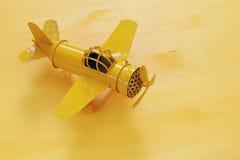 изображение ретро самолета игрушки желтого металла над деревянным столом Стоковые Фотографии RF