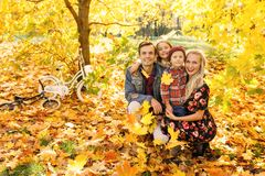 Изображение родителей и детей сидя в парке осени стоковые изображения