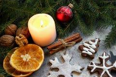 Изображение рождества Печенья в форме снежинок, floured, светов приведенных свечи, разбросанных кусков гаек, циннамона и апельсин Стоковая Фотография RF