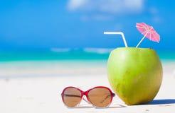Изображение свежего коктеиля кокоса и голубых солнечных очков на тропическом пляже Стоковое Изображение RF