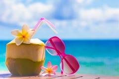 Изображение свежего коктеиля кокоса и розовых солнечных очков на тропическом пляже Стоковое Изображение
