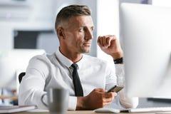Изображение серьезной рубашки бизнесмена 30s нося белой и связь сидят стоковая фотография