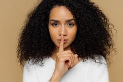 Изображение серьезной уверенной темной применять обложку к женщины делает shush жест, держит палец передней части над губами, гов стоковое фото