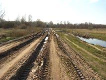 Сельская дорога с большими следами автомобилей и грязи Стоковые Фотографии RF