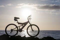 Изображение силуэта горного велосипеда на заходе солнца Стоковые Изображения RF