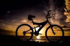 Изображение силуэта горного велосипеда на заходе солнца Стоковые Изображения