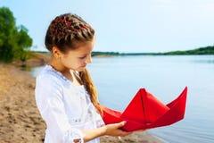 Изображение симпатичной девушки с красной бумажной шлюпкой Стоковое Фото