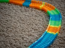 Изображение следа автомобиля игрушки и красочных элементов следа на ковре стоковое изображение rf