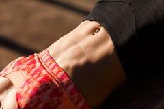 Изображение солнечных очков женщины спорт нося тренируя прессу в парке Стоковые Изображения RF