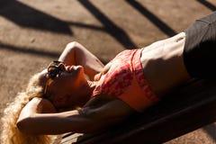 Изображение солнечных очков женщины спорт нося тренируя прессу в парке Стоковые Изображения