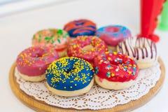 Изображение сортированных donuts в коробке при замороженный шоколад, украшает дырочками застекленный и брызгает donuts Стоковые Изображения RF