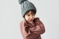 Изображение студии милой сердитой маленькой девочки со сварливой эмоцией в шляпе зимы теплой серой, нося свитером изолированным н стоковые фото
