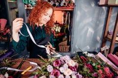 Изображение счастливой девушки с красными волосами используя ленту для того чтобы сделать составы Стоковые Фото