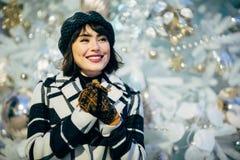 Изображение счастливой женщины на прогулке рядом с украшенным белым спрусом стоковые фото