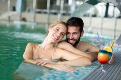 Изображение счастливых пар ослабляя в бассейне Стоковое Фото