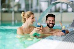 Изображение счастливых пар ослабляя в бассейне Стоковые Фото