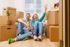 Изображение счастливых пар сидя на кресле среди картонных коробок стоковые фото