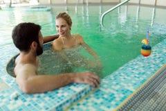 Изображение счастливых пар ослабляя в бассейне Стоковое Изображение