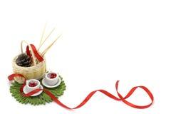 Изображение с красной лентой, 2 миниатюрными чашками и украшениями Стоковое Фото