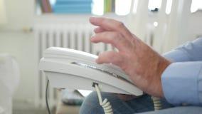 Изображение с человеком сидя на стуле в офисе делая нервные жесты рукой на телефоне видеоматериал