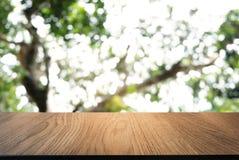 Изображение темного деревянного стола перед конспектом запачкало backgrou стоковое изображение
