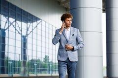 Изображение уверенно красивого молодого redhaired бизнесмена говоря на телефоне Стоковые Фото