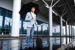 Изображение уверенно молодого redhaired бизнесмена держа черные зонтик и чемодан в дожде на стержне Стоковая Фотография