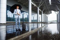 Изображение уверенно молодого redhaired бизнесмена держа черный зонтик в дожде на авиапорте Стоковые Изображения