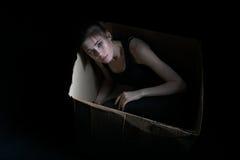 Изображение унылой маленькой девочки представляя в картонной коробке Стоковая Фотография RF