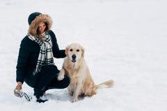 Изображение усмехаясь девушки с собакой в парке зимы Стоковые Изображения RF