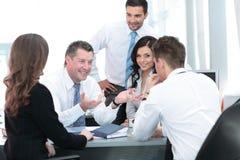 Изображение усмехаясь привлекательного бизнесмена работая в офисе Стоковые Изображения RF