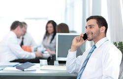 Изображение усмехаясь привлекательного бизнесмена работая в офисе Стоковые Изображения