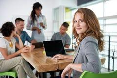 Изображение успешной вскользь бизнес-леди используя компьтер-книжку во время встречи стоковое изображение rf