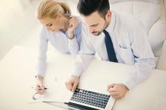 Изображение 2 успешных бизнесменов работая на встрече внутри  Стоковые Изображения