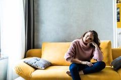 Изображение утомленной неопрятной женщины сидя дальше он укладывает дома Сериал ТВ вахты девушки новый Софа ослабляет концепцию п стоковое фото
