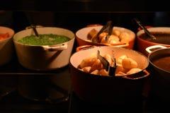 Изображение фотографии еды больших лотков или баков заполнило горохи и подливку золотых картошек жаркого цвета кудрявых зеленые н Стоковое Фото